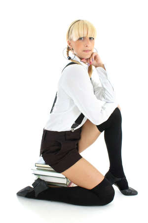 cute schoolgirl sitting on stacked books Stock Photo - 7626589