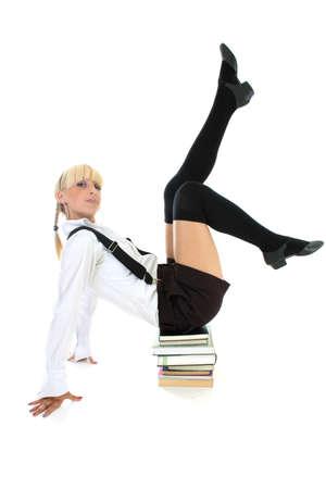cute schoolgirl sitting on stacked books Stock Photo - 7631574