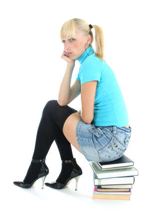 sad schoolgirl in blue sitting on stacked books photo
