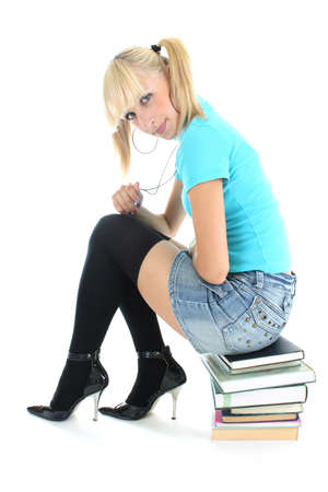 cute blondie schoolgirl sitting on stacked books photo