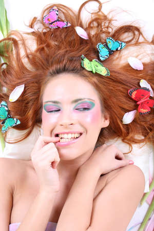 Red-haired woman with butterflies on her head lying photo
