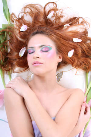 sexy red-haired woman with petals lying photo