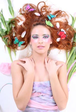 young red-haired woman with butterflies and petals on her head lying photo