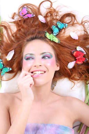 young red-haired woman with butterflies and petals on her head lying biting her finger photo