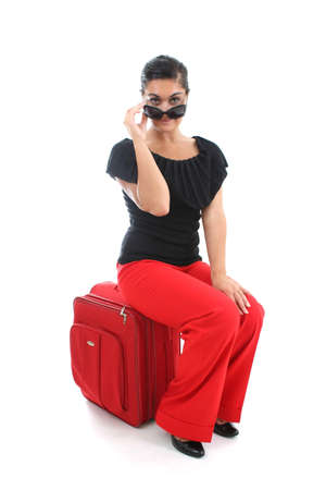 young businesswoman in sunglasses sitting on big suitcase photo