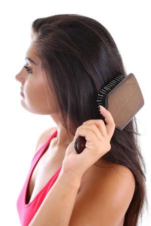 young pretty woman in pink brushing her hair photo