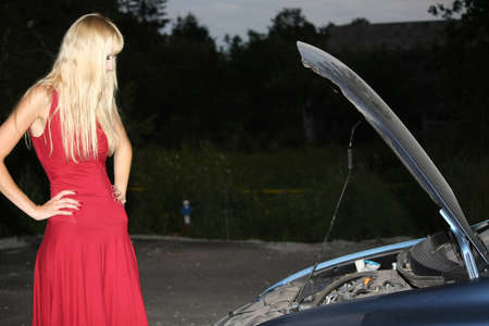 blond woman in red dress with broken car photo