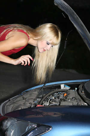 blond woman in red dress repairing a broken car photo