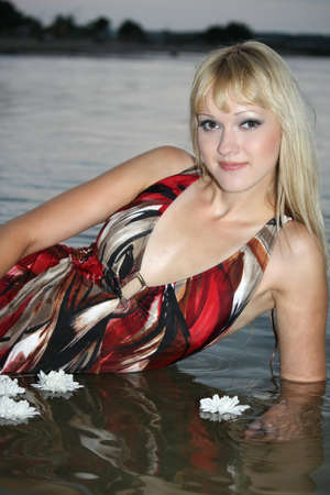 sexy blond woman lying in water with white flowers photo