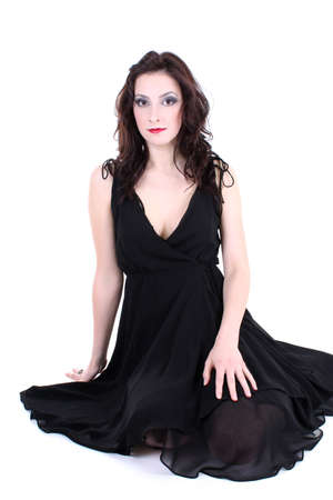brunette with red lips and smoky eyes in black dress sitting