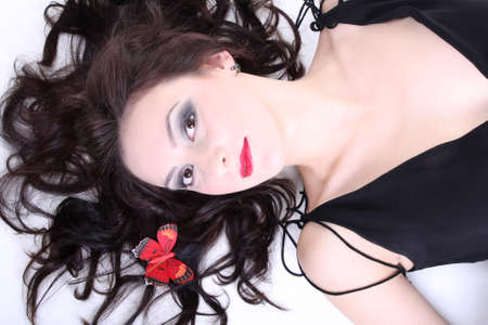 brunette with red lips and smoky eyes in black dress lying Stock Photo - 7753895