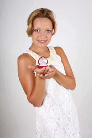 smiling bride holding wedding rings in red box. focus on rings photo