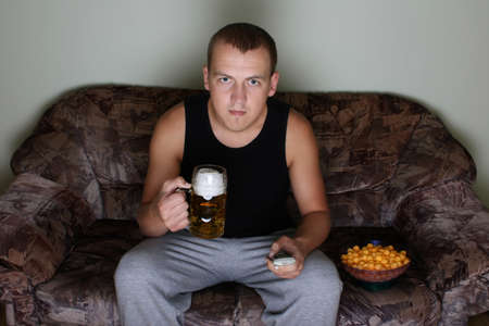 young man watching tv with beer