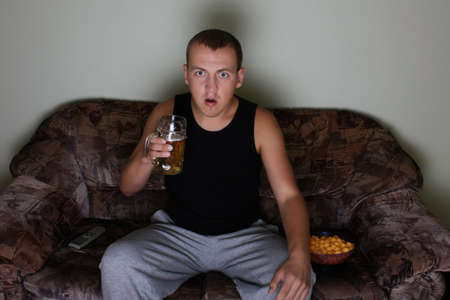 interested: young interested man watching tv with beer and chips Stock Photo