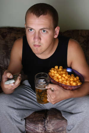 holiday movies: young man watching tv with beer and chips