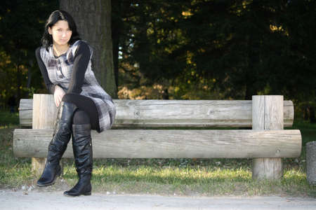 young attractive woman posing on bench in park photo