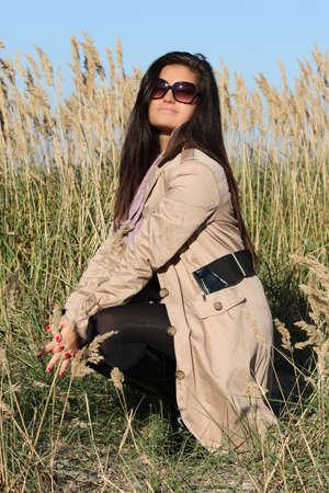 woman in beige autumn coat and sunglasses photo