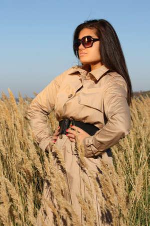 beautiful woman in beige autumn coat and  sunglasses posing photo