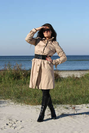 beautiful woman in beige autumn coat and  sunglasses posing by the sea photo