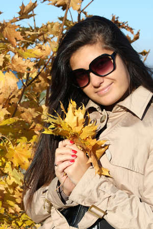 young beautiful woman in beige autumn coat with golden leafage photo