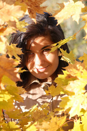 young beautiful woman with golden leafage photo