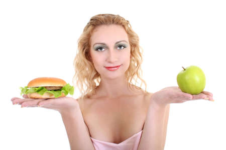 young beautiful woman with green apple and hamburger over white Stock Photo - 8050159