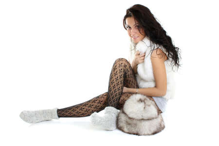 beautiful woman with fur hat  sitting over white background photo