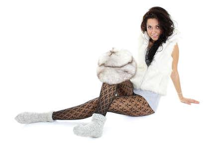 schöne Frau mit Pelzmütze sitzend over white background
