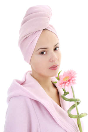 Young beautiful woman in bathrobe with towel on head and gerberas in hand photo
