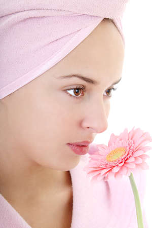 Portrait of young beautiful woman in bathrobe smelling gerberas photo