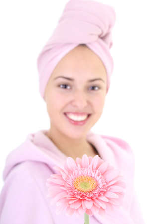 Young beautiful woman in bathrobe with gerberas after bath.Focus of flower photo