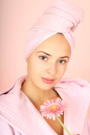 Young beautiful woman in bathrobe with towel on head and gerberas in hand over pink photo