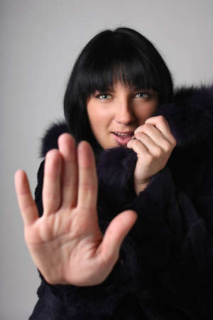 Young woman in fur coat making stop gesture over grey background photo