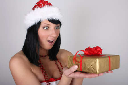 Surprised brunette woman in santa hat with golden gift  over grey background photo