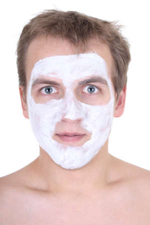 young man with cosmetic mask on his face over white photo