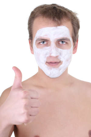 young man with cosmetic mask on his face thumbs up over white photo