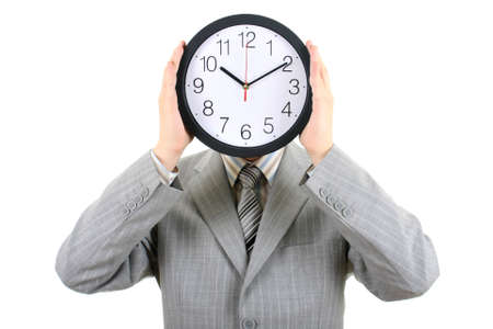 man in gray suit holding big clock covering his face over white photo