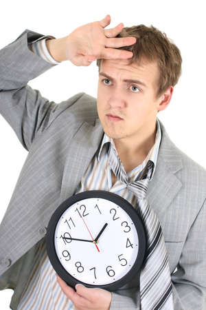 Tired businessman in grey suit holding a clock over white photo