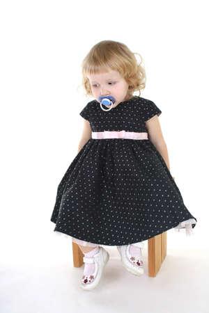 sad little girl in black dress sitting over white photo