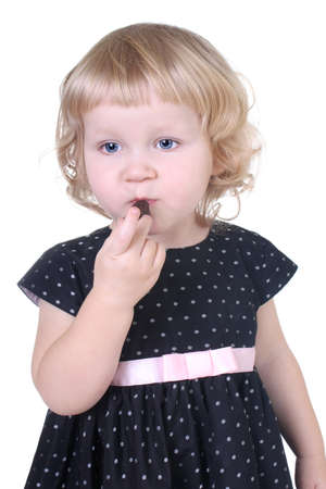 little girl with chocolate candy over white photo