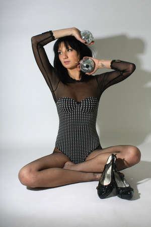 Sexy woman in black with discoball sitting photo