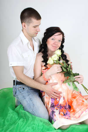 Pregnant wife with roses and her husband sitting Stock Photo - 9323042