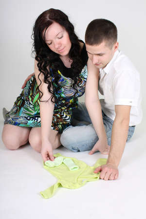 Happy couple looking on little green baby clothes photo
