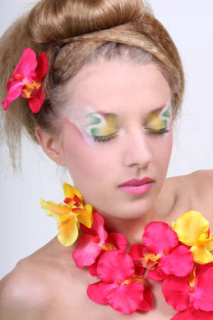 Beautiful woman with creative make-up, coiffure and flowers photo