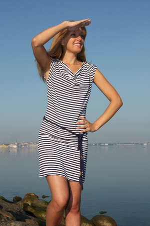 suntanned: Woman in dress with stripes near the sea