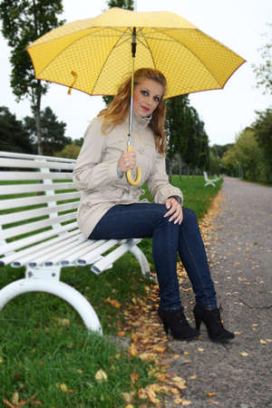 Happy woman with yellow umbrella sitting on bench photo