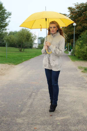 wet jeans: Beautiful woman with yellow umbrella in the park