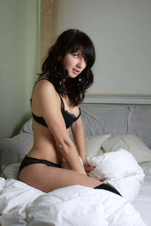 sexy beautiful brunette sitting on bed