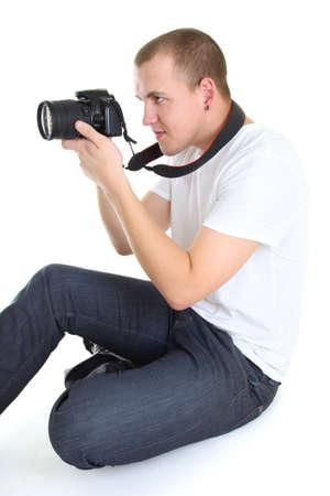 photographer with dslr camera sitting isolated over white background photo