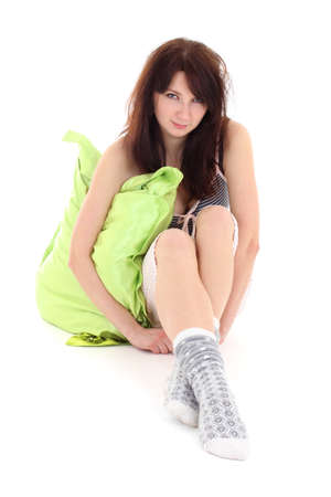 slumberous: sleepy girl in pajamas sitting with pillow over white Stock Photo